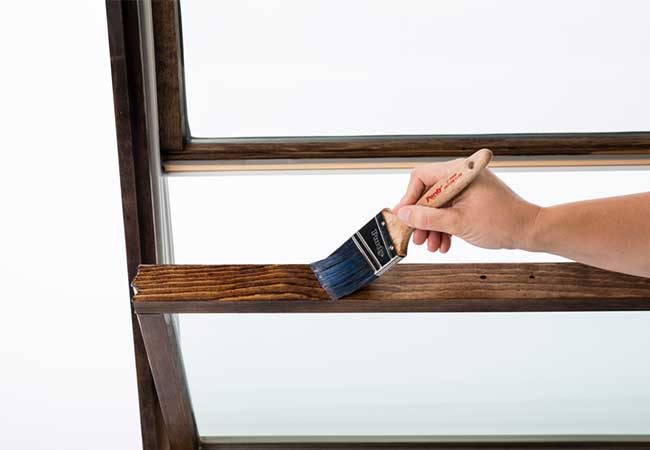 A hand holding a paintbrush staining the bottom sash of a wood double-hung window.