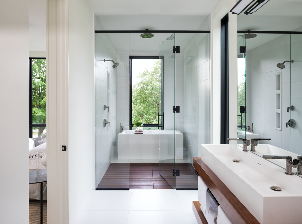 Long bathroom with a separate room for the bathtub with a large black window overhead