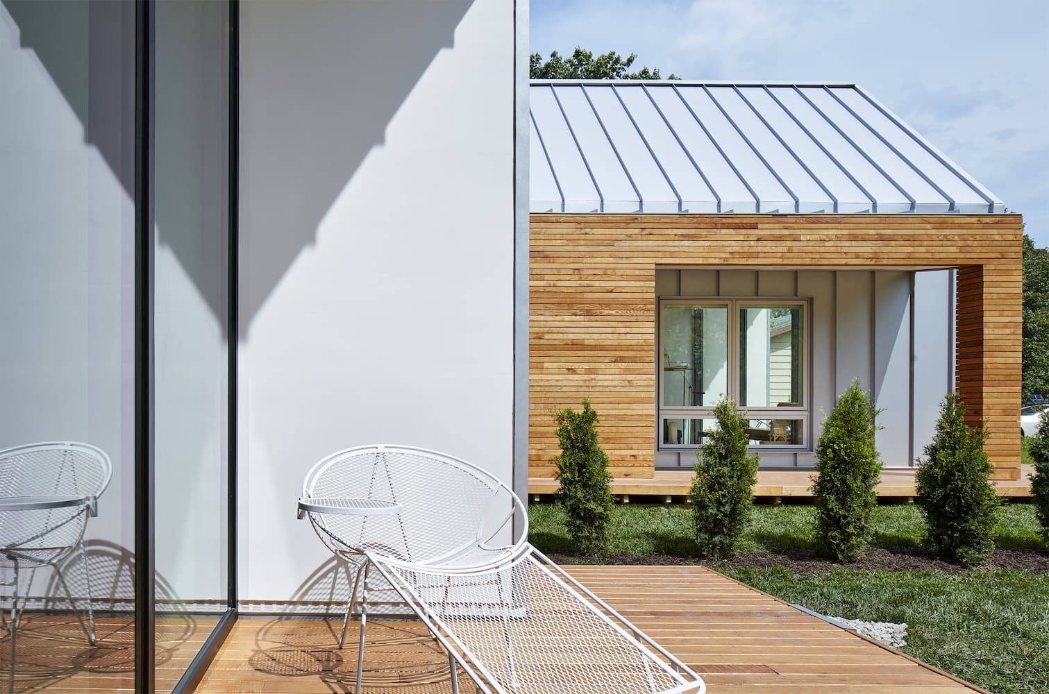 Patio on modern home has a chair alongside large white picture window