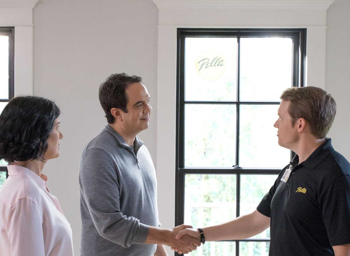 Replacement window consultation with customer shaking hands with Pella rep