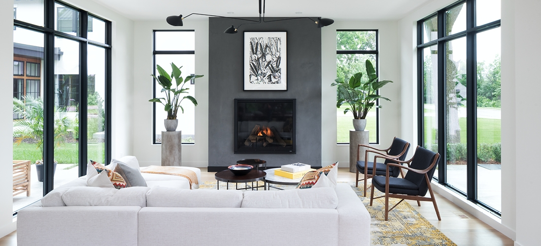 white modern living room surrounded by wood windows
