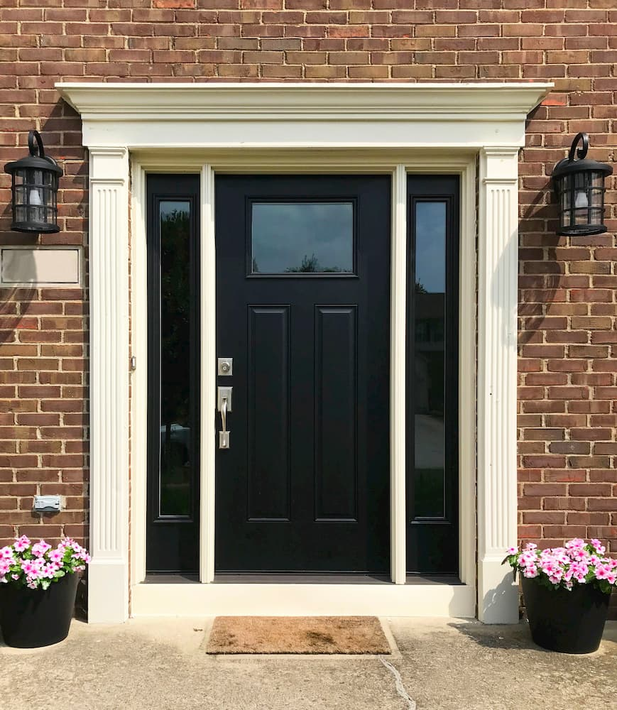 Black front door with matching sidelights on each side surrounded by elegant white trim