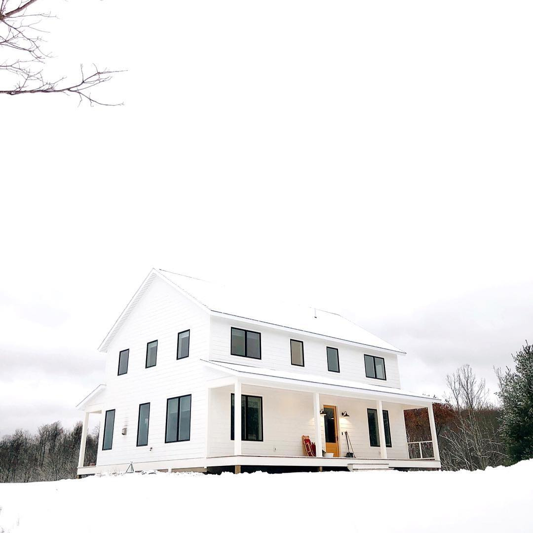 White farmhouse with black casement windows on snowy day