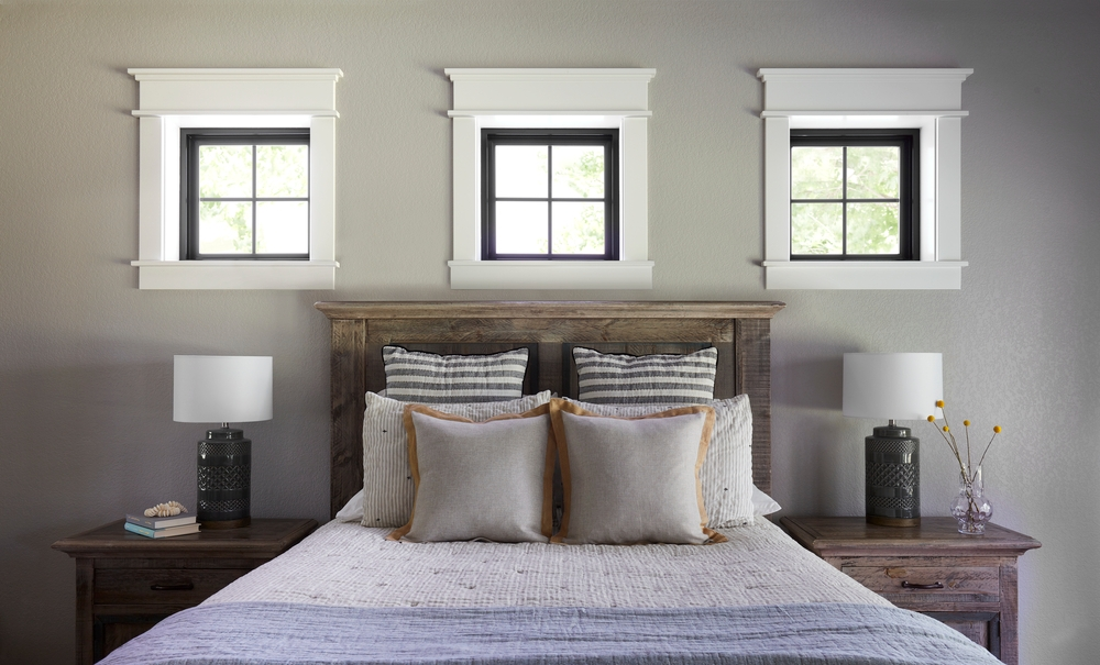 Three square black windows with white trim above bed