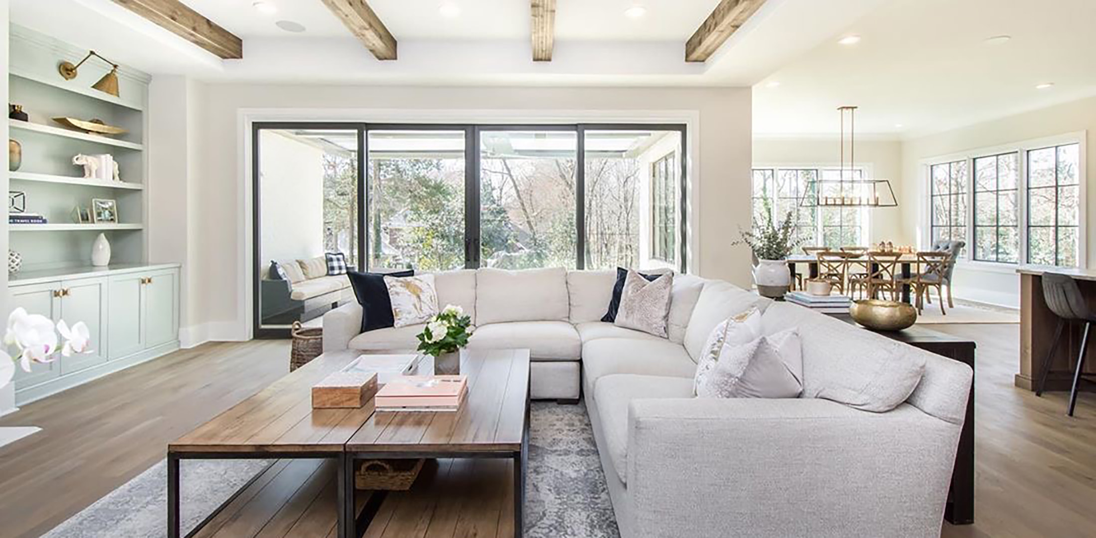 A cozy open floor plan home features a wall of black sliding patio doors connecting the living room with outdoor seating.