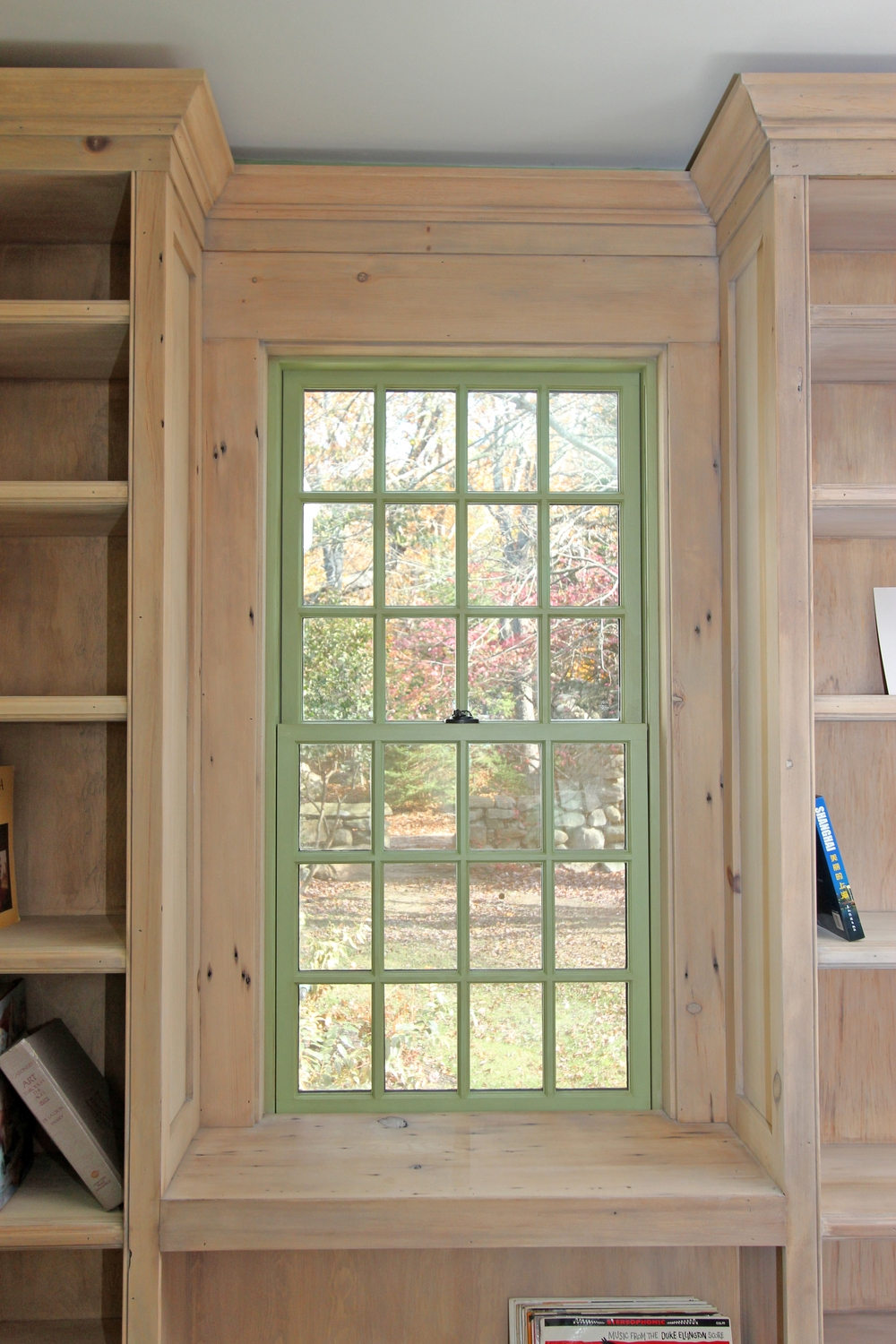 green double-hung window surrounded by natural wood bookcase on either side