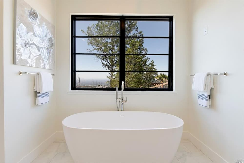 Black windows with horizontal grilles contrast against white bathroom
