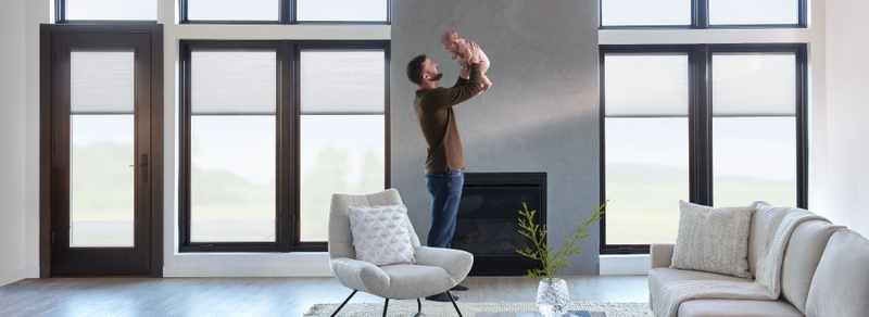dad and baby in a living room in front of a wall of windows and hinged door