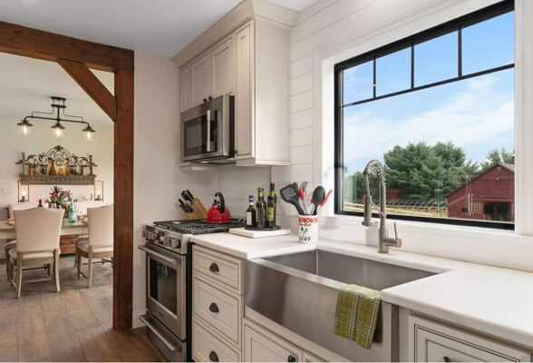 Farmhouse style kitchen with black picture window over the sink