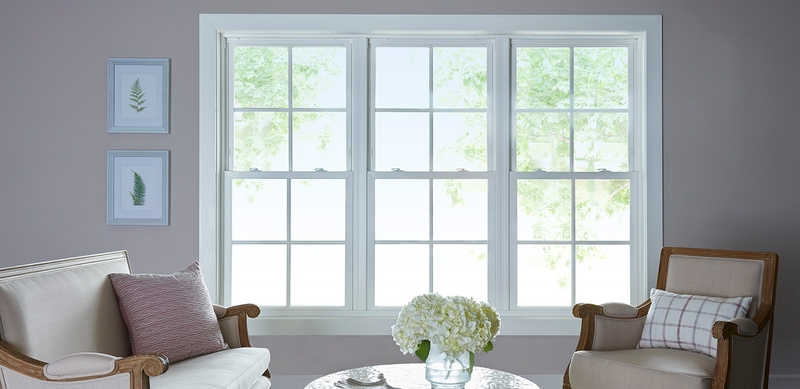 three pella 250 series windows with white trim and traditional grilles