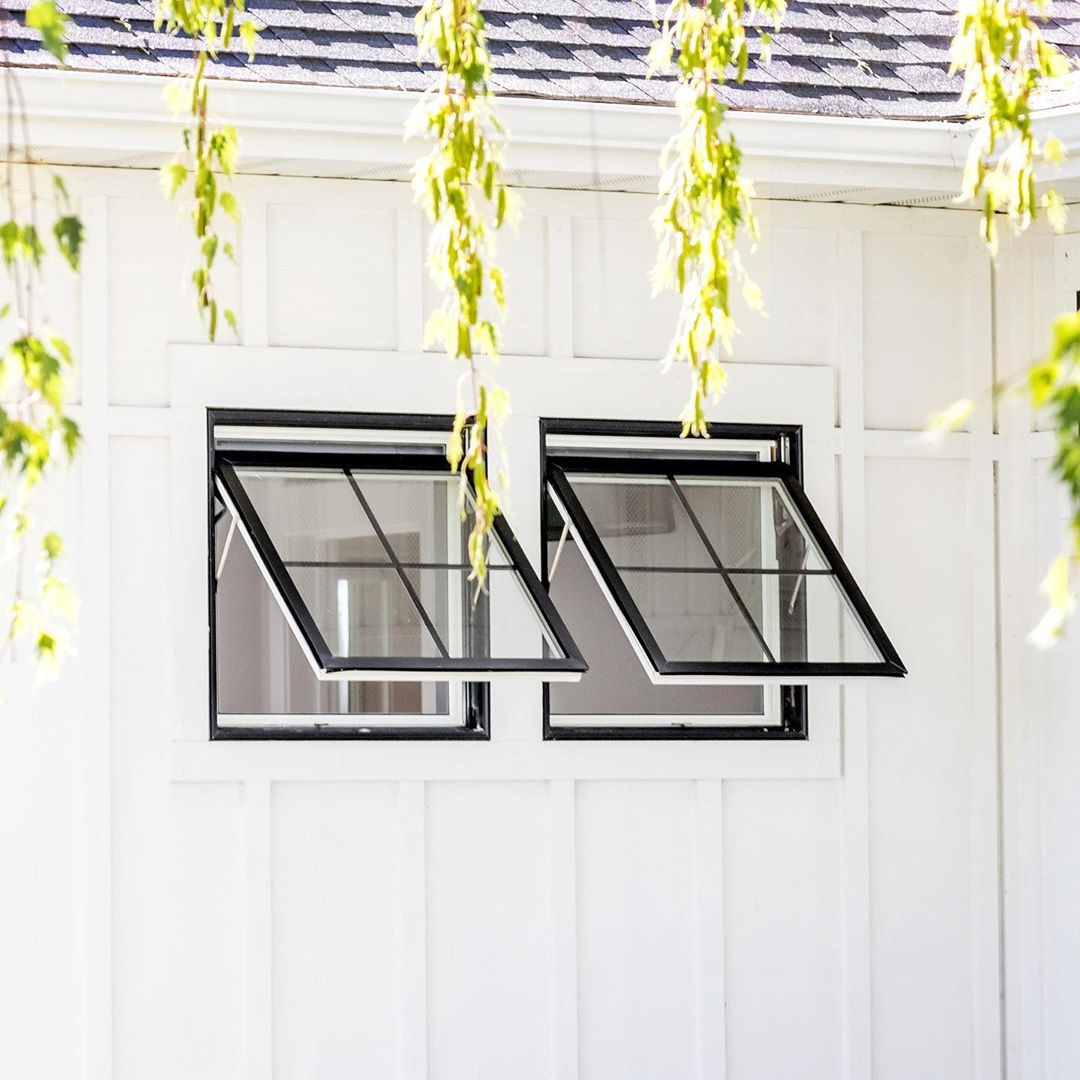 white siding with two black awning windows open and tree limbs hanging down