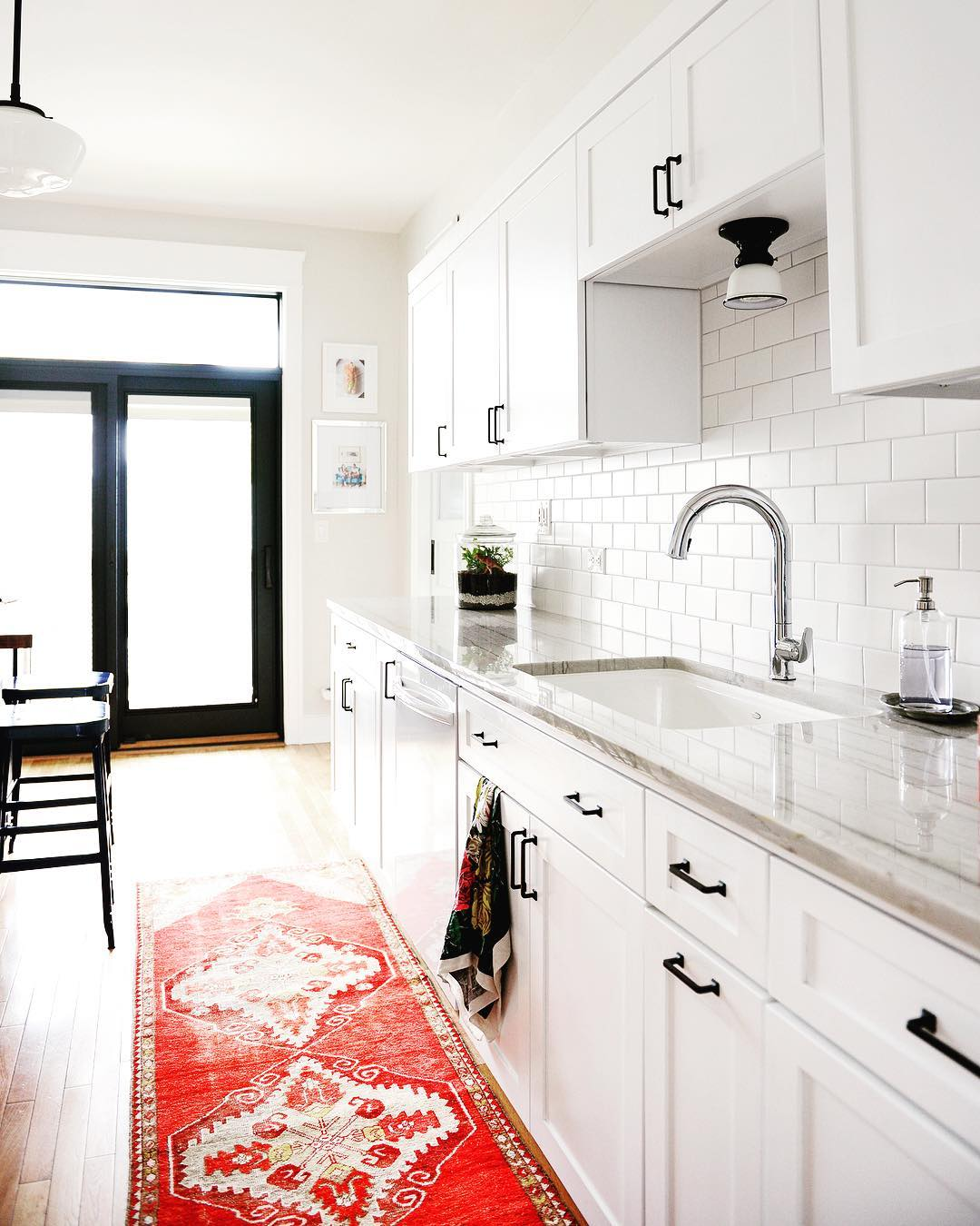 contemporary white kitchen with red rug and black patio door