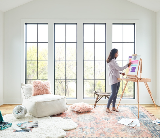 girl painting in front of 3 large picture windows