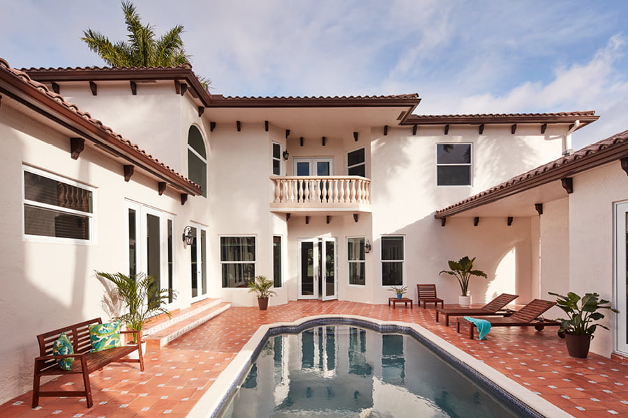 Exterior white home with Hurricane Shield windows, red tiled outdoor space and pool