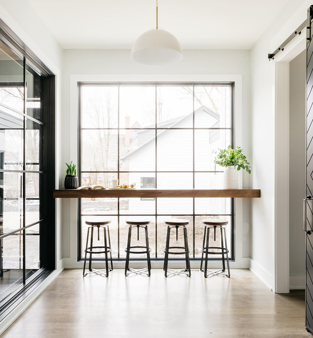 A floor-to-ceiling picture window with grilles behind a long countertop adds to modern kitchen.