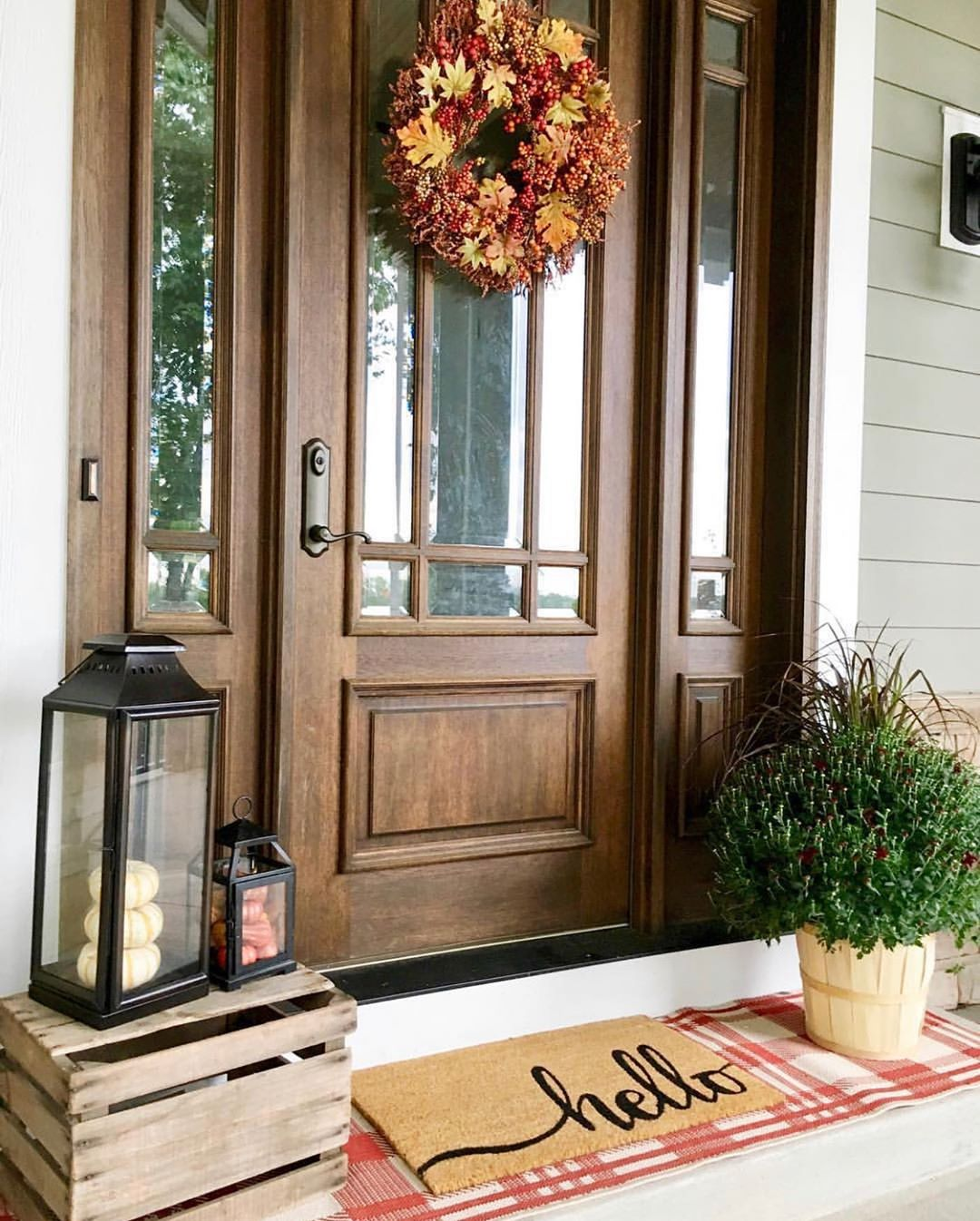 Wood stained front door with glass and matching sidelights surrounded by seasonal décor