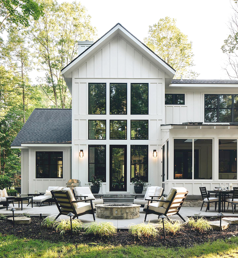 The exterior of a white farmhouse has black picture windows and a black hinged patio door, opening to a fire pit patio.