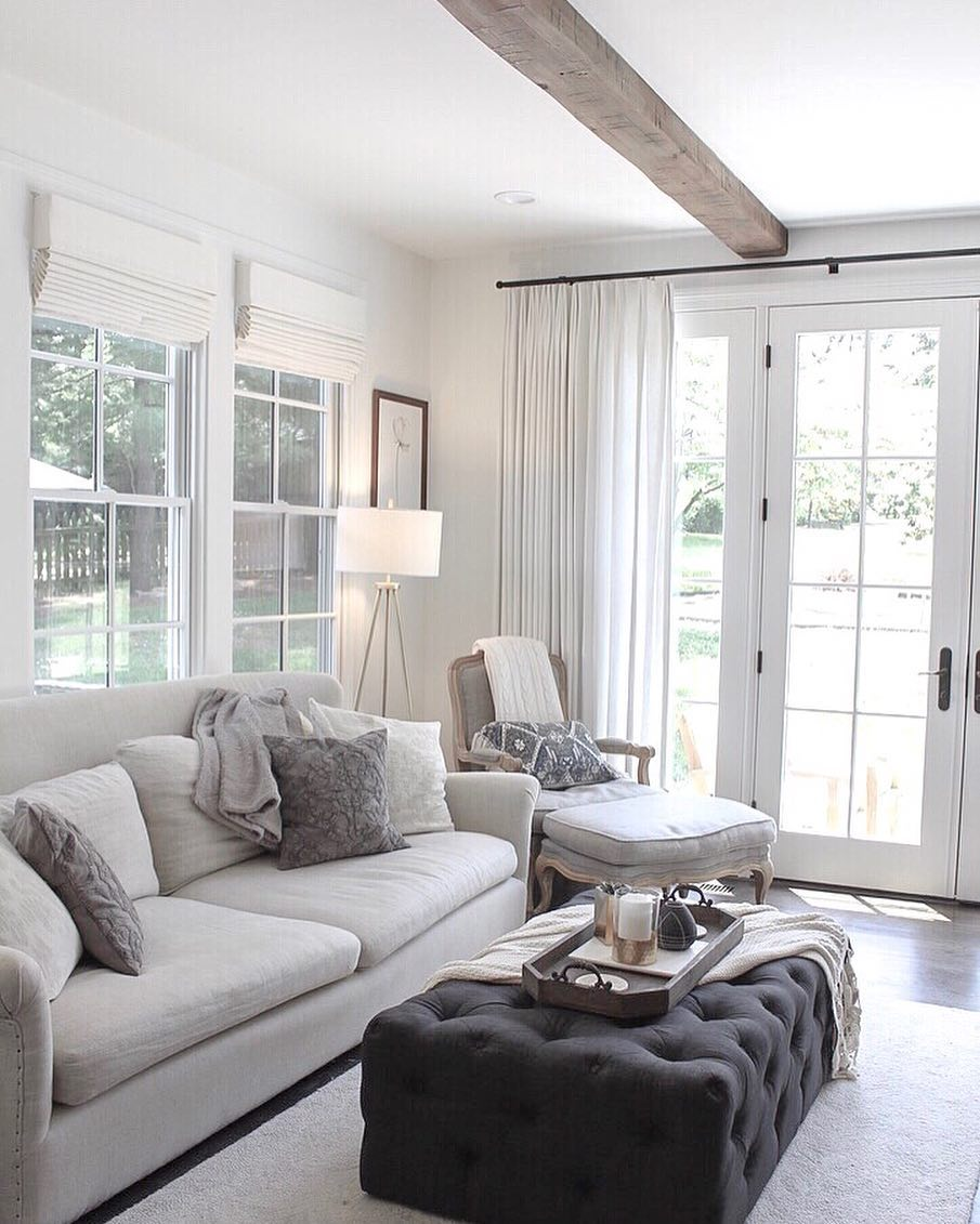 white on white living room couch, chair, and gray ottoman next to set of white french doors
