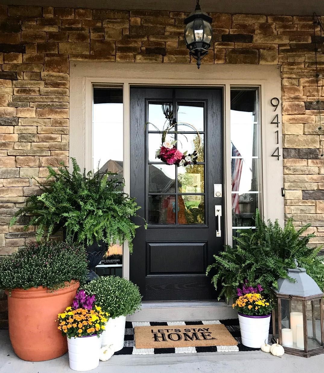 Black farmhouse style front door on brown brick house surrounded by plants