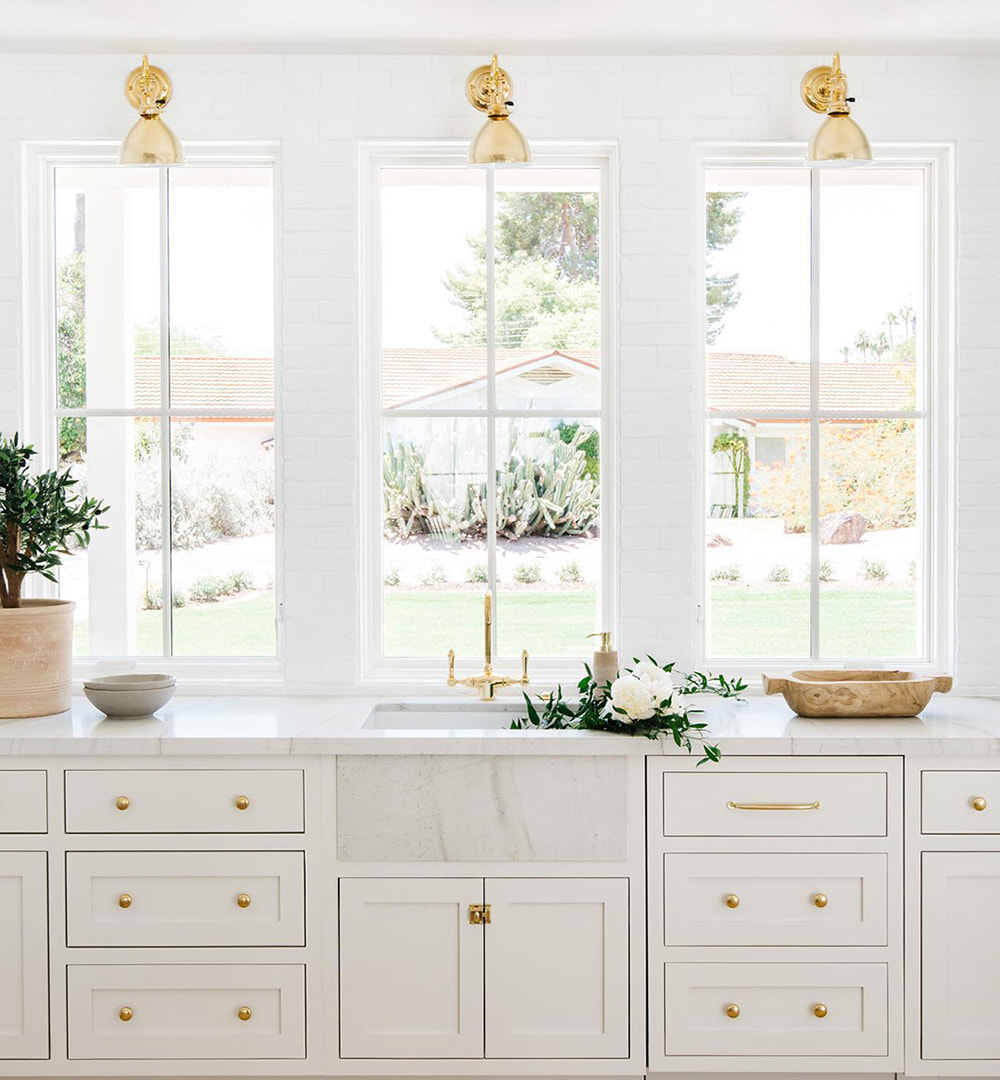 White kitchen with gold hardware features three traditional windows with simple grilles over the sink.