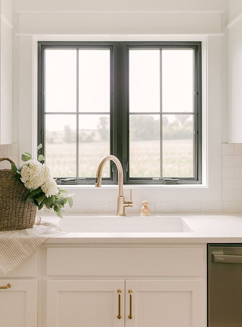 A white kitchen with gold hardware has two black casement windows over the sink.