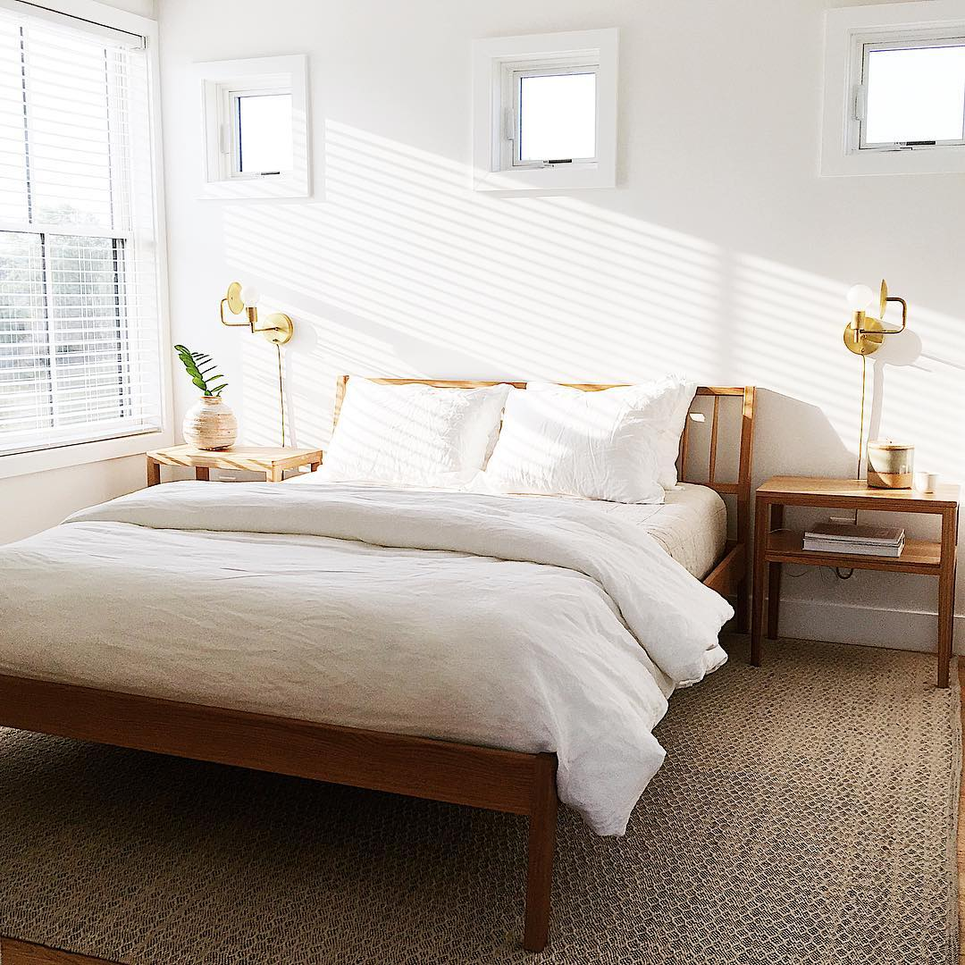 light streaming into white bedroom through large double-hung window with three square windows above bed