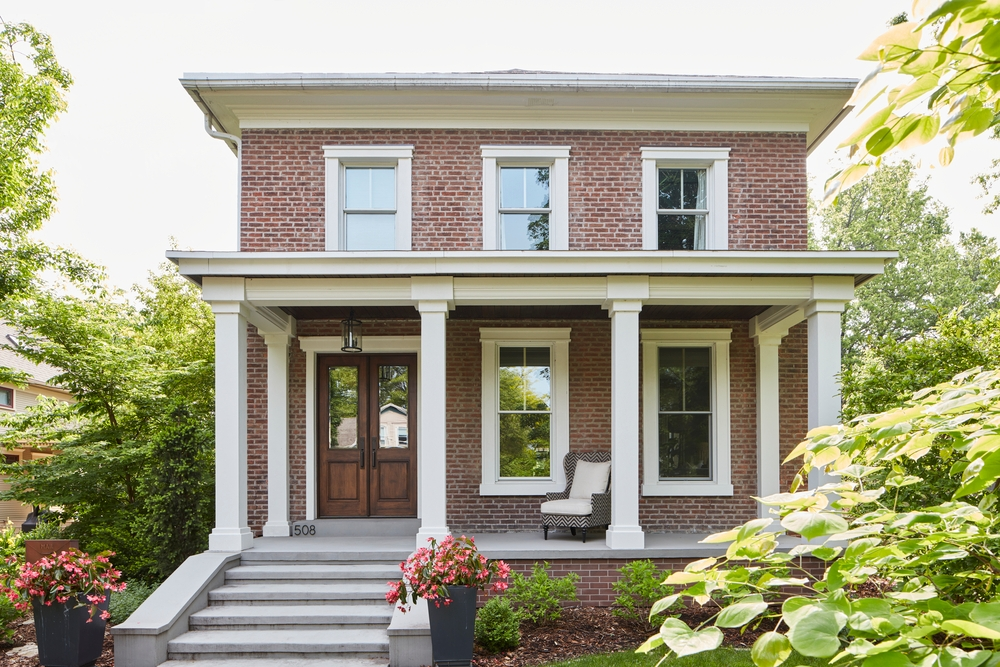 Two story red brick house with white double-hung windows and a wood double door with glass