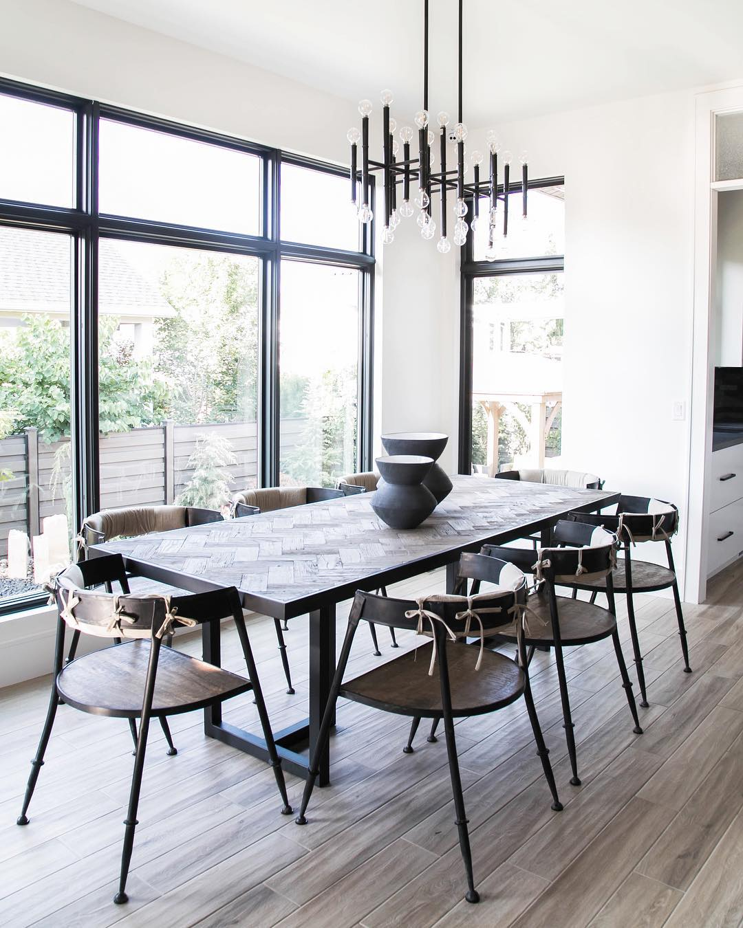 Wall of black picture windows in modern dining room
