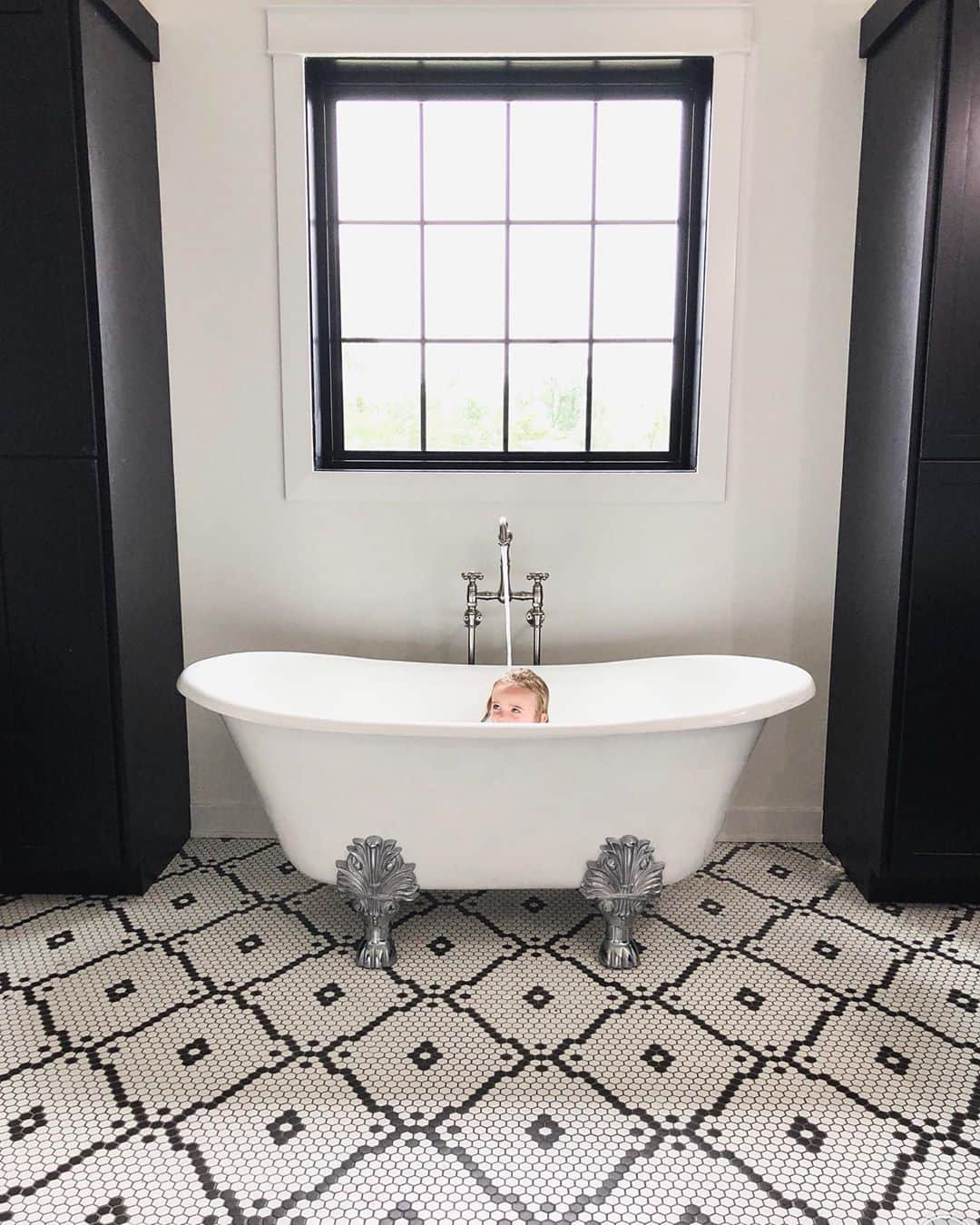 black and white bathroom with face peeking out of the freestanding tub and black picture window directly above