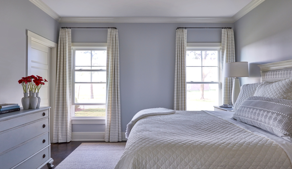 Neutral colored bedroom with bed in front of two double-hung vinyl windows with white & gray striped curtains