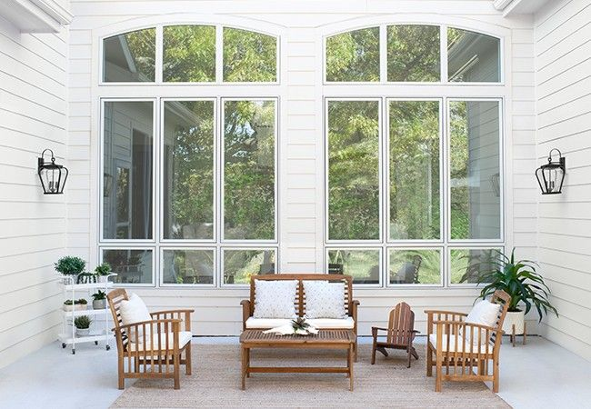 White and wood deck furniture by tall, white fixed-frame windows