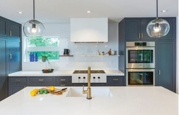 Modern kitchen with charcoal cabinets, white countertops & windows, and gold accents