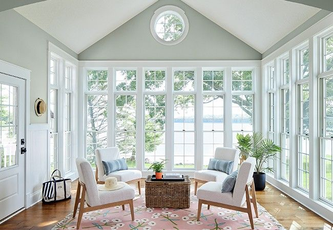White single-hung windows in a sunroom with white chairs and an ocean view