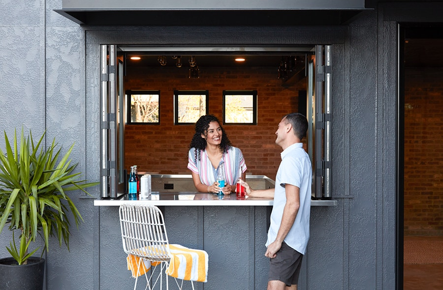 Two people standing around bar top walking between open pass-through windows