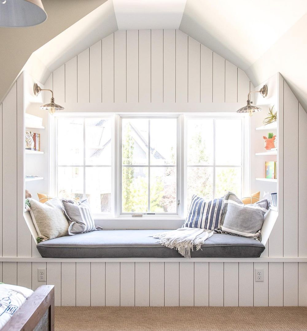 A bedroom window seat adorned with decorative pillows lies below white casement windows.