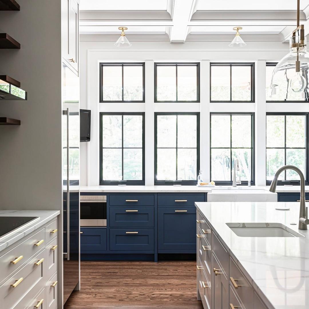 Two rows of black windows with grilles illuminates modern farmhouse kitchen