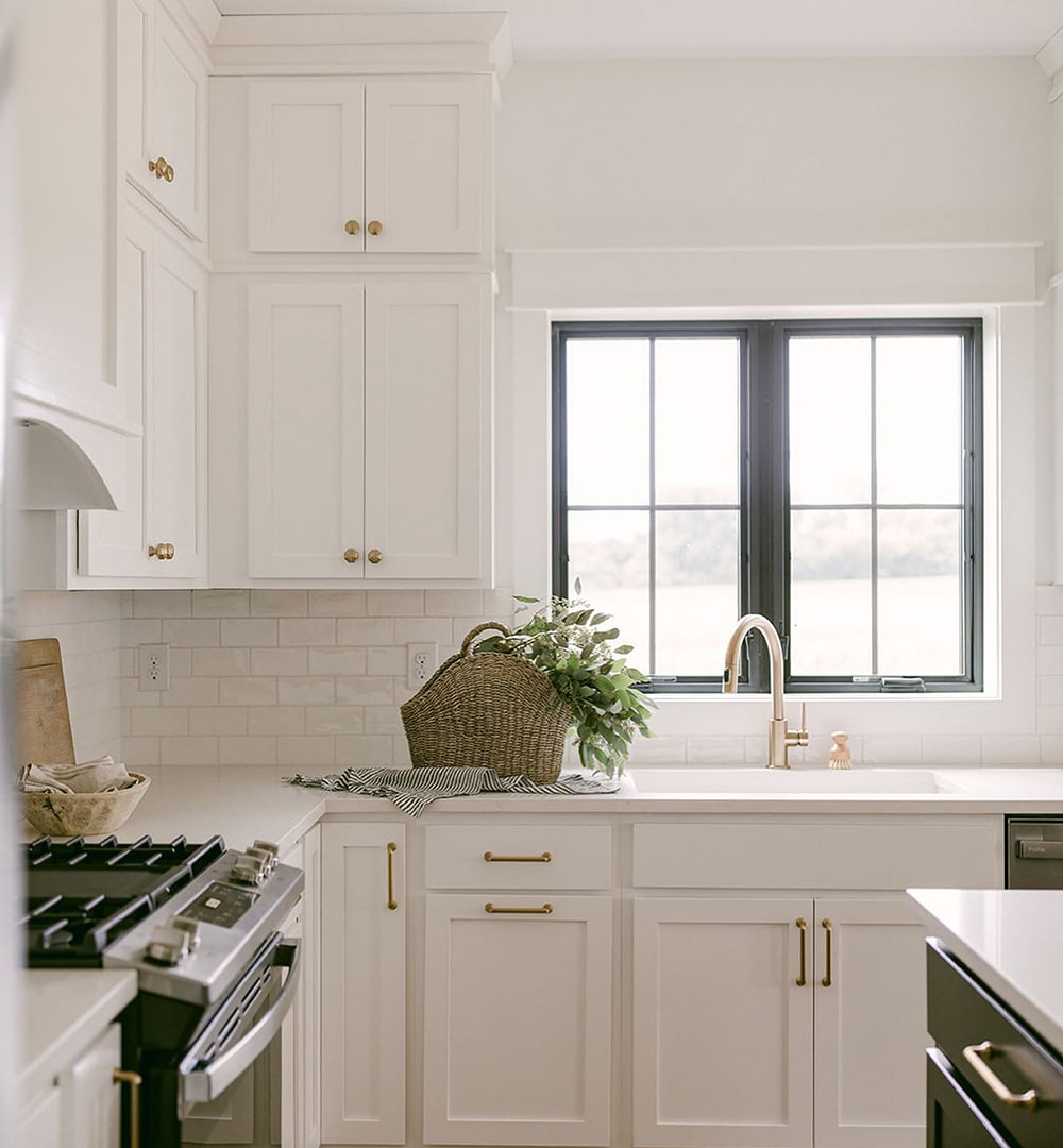 Two black casement windows above the kitchen sink match the cabinet color on the kitchen island.