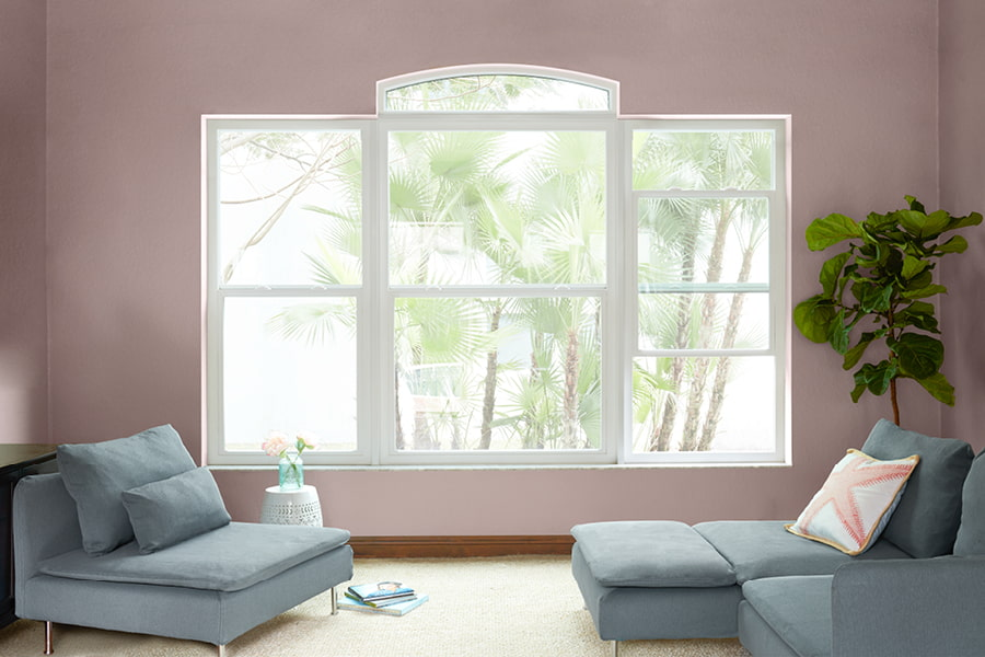 3 white framed windows with a transom in a pink living with green furniture