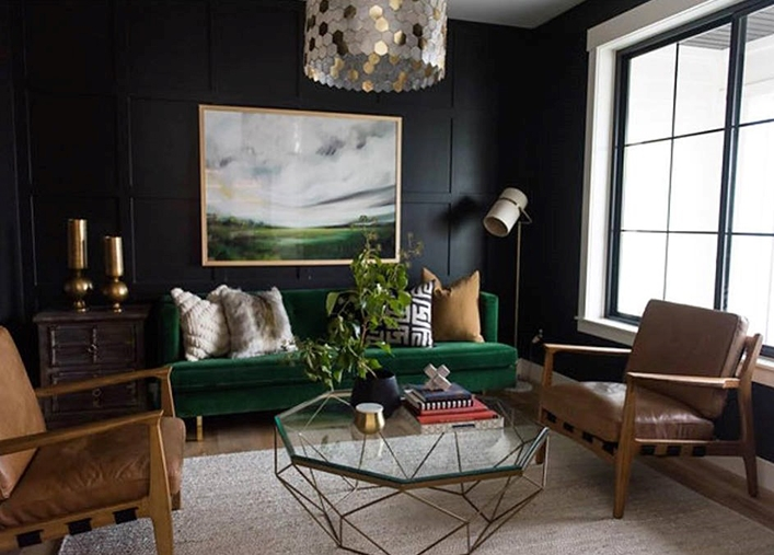 large black windows light living room with black walls, green couch, and brown leather chairs