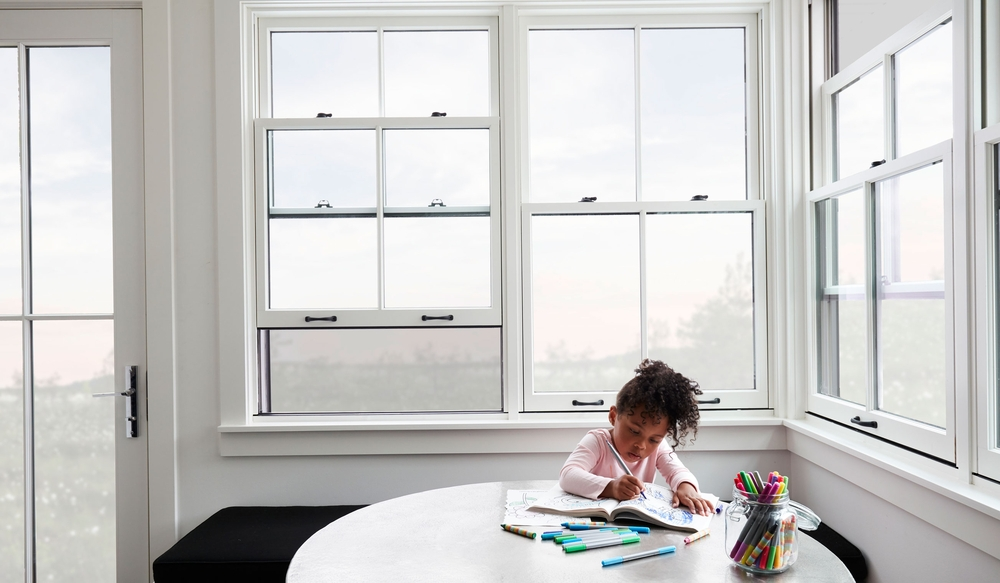 girl coloring at table with white double-hung windows with integrated screen behind her