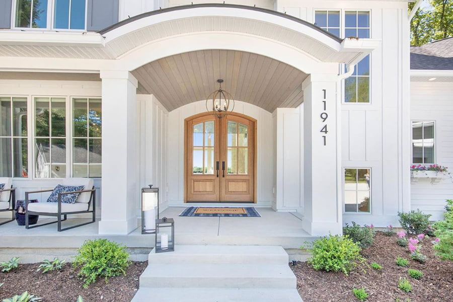 White Sherwood Homes with double wood entry doors