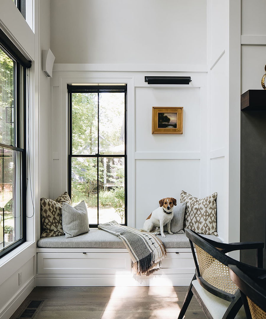A dog sits on the window seat below black double-hung windows in a contemporary dining room.