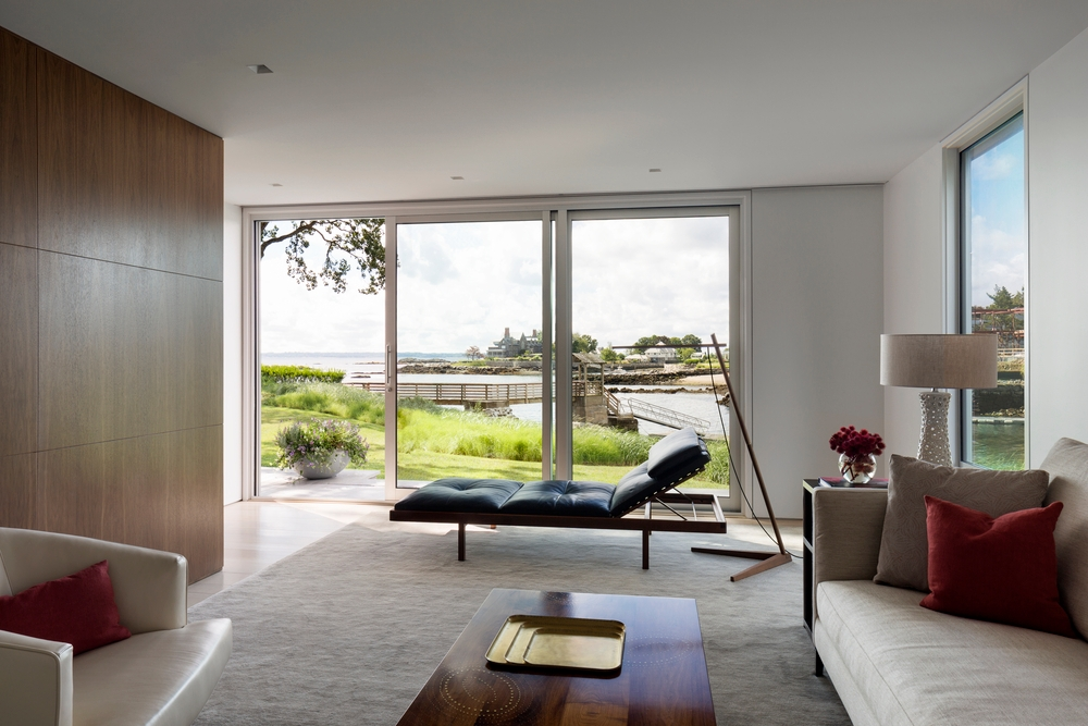 Minimalist designed living room with large sliding patio door overlooks lakeside view