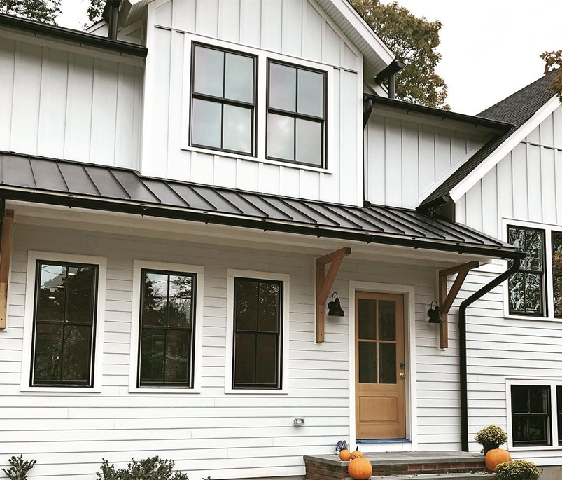 White modern farmhouse with black double-hung windows and wood stained front door