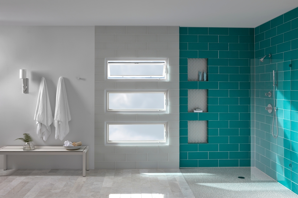 Teal tile shower next to a stack of three awning windows with the top window vented
