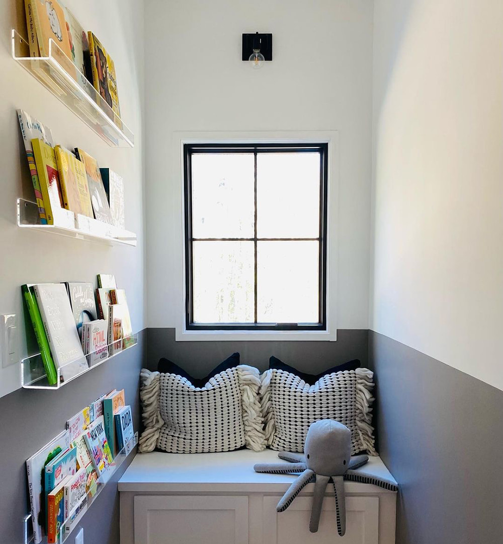 A small nook in a bedroom features shelves of books on the wall and a window seat below a black casement window.