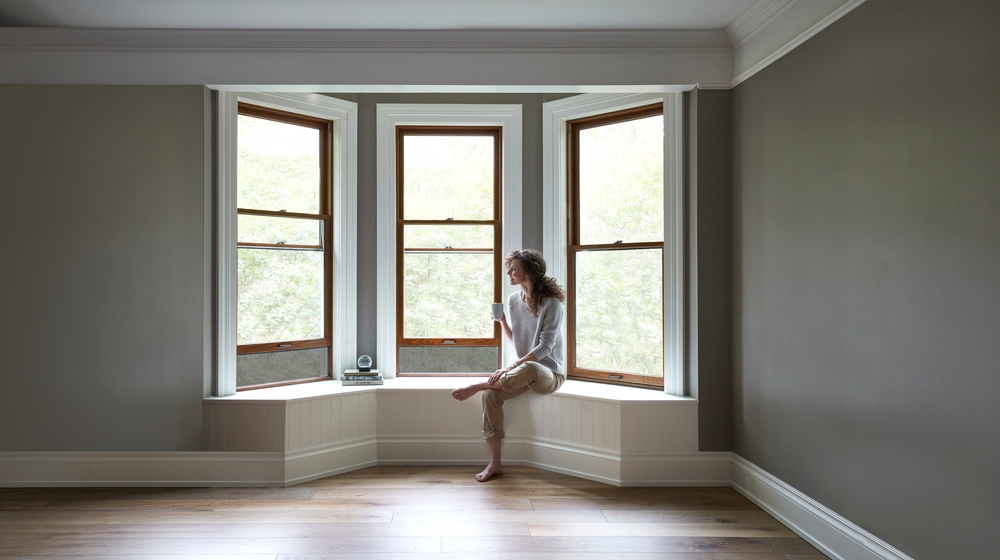 Wood stain bay windows with white trim and woman sitting on window seat
