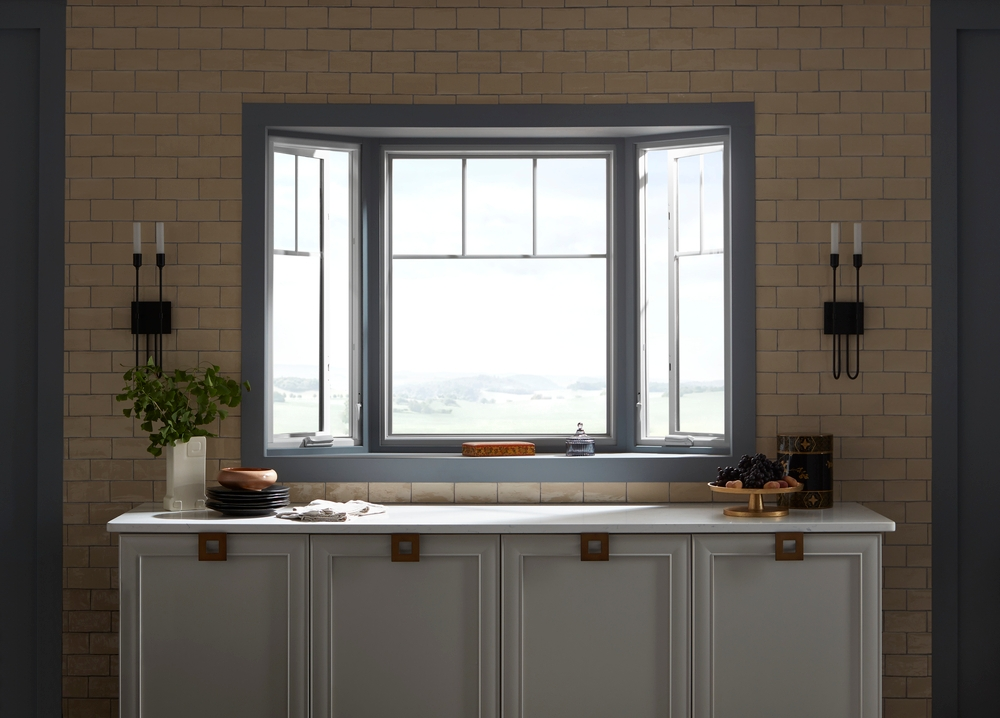 Bay window with white frames and blue trim directly above kitchen counter