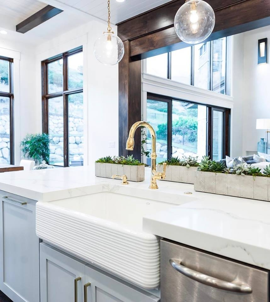 farmhouse sink in contemporary kitchen with large mahogany stain picture windows behind