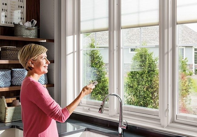 Woman using smart blinds remote.
